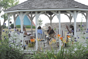 Alumni meet and talk in a gazebo