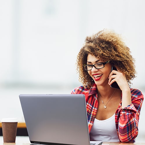 Smiling female individual in a white top and flannel button-down talking on a mobile phone working on a laptop outside