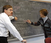 Two professors explain advanced concepts to students on a chalk board.
