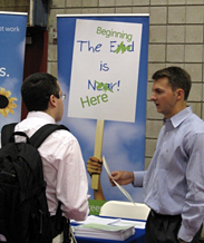 A student handing his resume to an employer at a career fair.