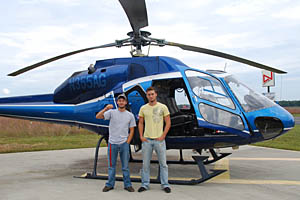 Two students pose outside of a blue media helicopter