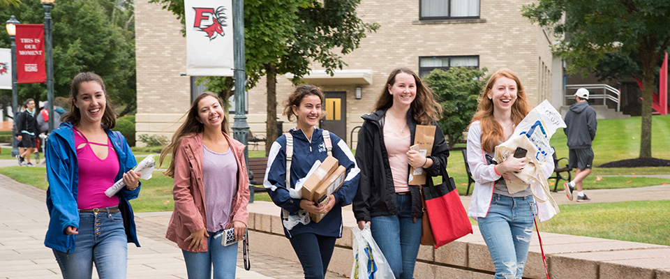 Image of Fairfield University students walking with mail and packages in hand
