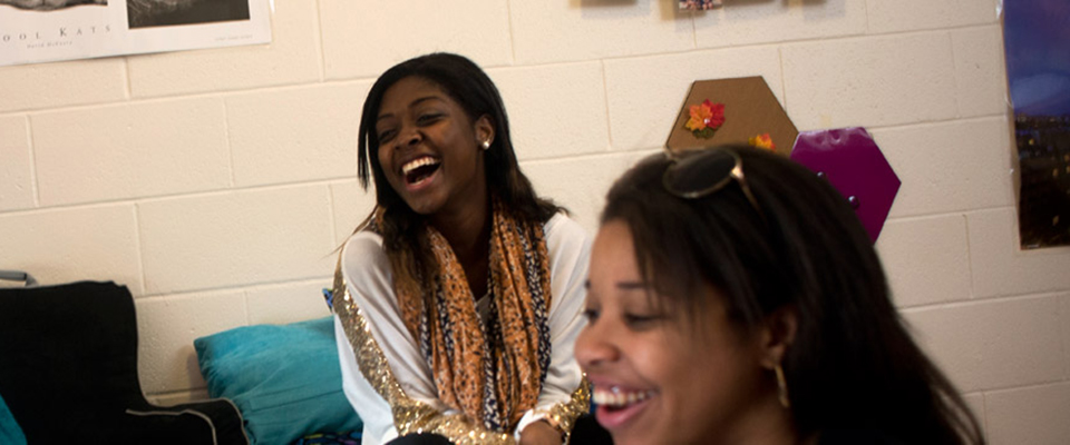 Two girls laughing in a dorm room