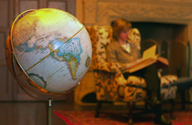 A woman reads next to a globe at the library