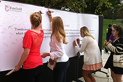 Fairfield University students signing a banner pledging to be academically honest.