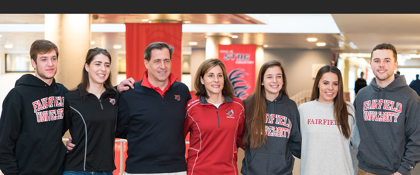 A family, arm in arm, wearing Fairfield University shirts, jackets and hoodies.