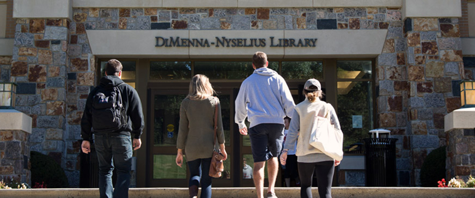 A group of students entering the DiMenna-Nyselius Library