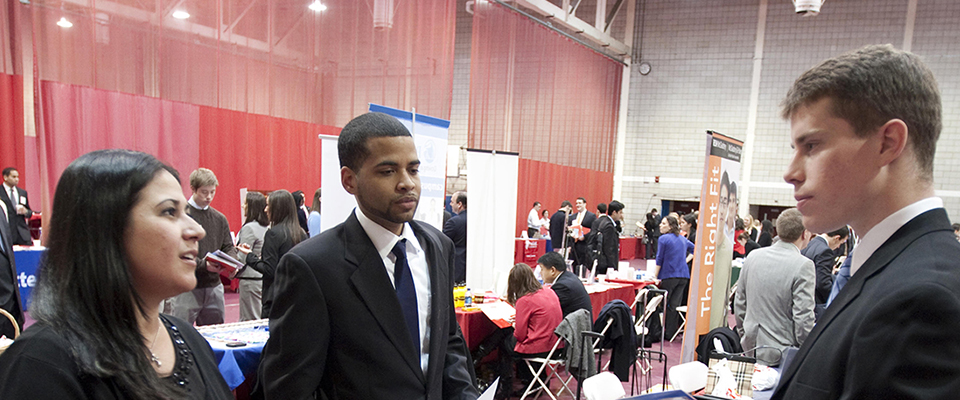 An upperclassman gets a chance to talk to some employers at a career fair.