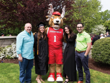 Parents pose with Lucas the Stag during their student's Fairfield University graduation