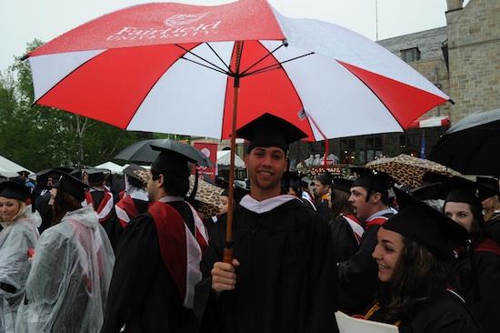 Fairfield University Stag graduate holding an umbrella at a rainy Commencement ceremony amongst fellow graduates