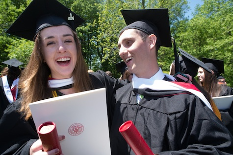 Fairfield University Stag graduates holding their diploma holders while posing and smiling for the camera